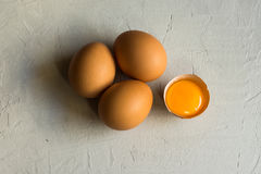 Fresh organic brown eggs, cracked shell, open bright yolk on white concrete table surface, top view, abstract stock photo