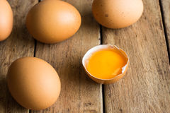 Fresh organic brown eggs scattered on wood table, open yolk, minimalistic, Easter royalty free stock photography