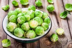 Fresh organic Brussels sprouts in a bowl. On a wooden table Royalty Free Stock Photos