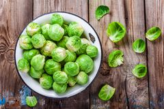 Fresh organic Brussels sprouts in a bowl. On a wooden table Stock Photography