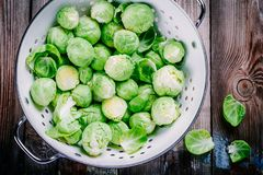 Fresh organic Brussels sprouts in a colander. On a wooden table Royalty Free Stock Photos