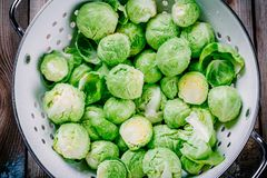 Fresh organic Brussels sprouts in a colander. On a wooden table Stock Photos