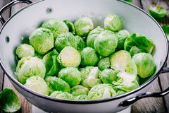 Fresh organic Brussels sprouts in a colander. On a wooden table Royalty Free Stock Images