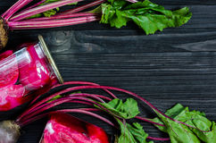 Fresh Organic and Canned Beetroots Background. Canned homemade beetroot in clear glass jars with fresh organic beetroots on a black wooden background top view Stock Images