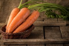 Fresh Organic Carrots in a basket on wooden background Royalty Free Stock Photos