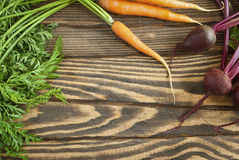 Fresh organic carrots and beets with tops on a wooden table. Top view Royalty Free Stock Photo