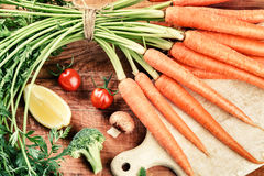 Fresh organic carrots bunch in cooking setting. Healthy eating c Royalty Free Stock Photography
