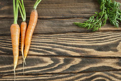 Fresh organic carrots with tops on a wooden table. Top view Stock Photos