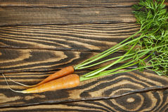 Fresh organic carrots with tops on a wooden table. Top view Royalty Free Stock Photography