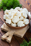 Fresh organic cauliflower cut into small pieces. In ceramic bowl on wooden background Royalty Free Stock Photo