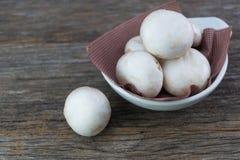 Fresh organic champignon mushrooms in white bowl on wood backgro. Und Royalty Free Stock Photos