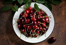 Fresh organic cherries in a vintage white bowl on a brown concrete background. Stock Photo