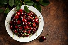 Fresh organic cherries in a vintage white bowl on a brown concrete background. Royalty Free Stock Photography