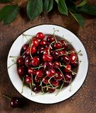 Fresh organic cherries in a vintage white bowl on a brown concrete background. Royalty Free Stock Images