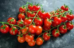 Fresh organic cherry tomatoes on black table stock photo