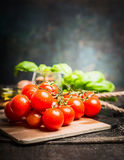 Fresh organic cherry tomatoes on vintage kitchen table over dark background Stock Photos