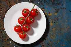 Fresh organic cherry tomatoes on white plate and dark background Royalty Free Stock Photo