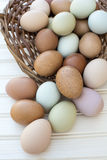 Fresh organic chickeneggs overflow out of basket on wooden backg Stock Image