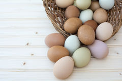 Fresh organic chickeneggs overflow out of basket on wooden backg Stock Photo