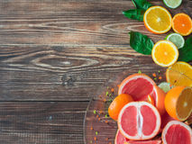 Fresh organic citruses. Oranges, limes, tangerines and grapefruiton dark wooden background. Top view with copy space Royalty Free Stock Images
