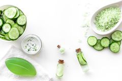 Fresh organic cosmetics with cucumber. Cream, lotion, spa salt on white background top view copyspace Royalty Free Stock Photography