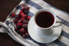 Fresh Organic Cranberry Juice. Organic Cranberry Juice in a white cup and frozen cranberry on an kitchen towel Royalty Free Stock Photography