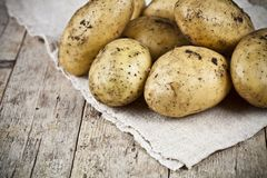 Fresh organic dirty potatoes heap closeup on linen tablecloth on rustic wooden background. Newly harvested potatoes royalty free stock photography