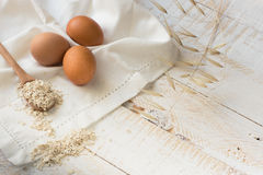 Fresh organic eggs,dry oatmeal flakes on wooden spoon scattered over white linen cloth, Royalty Free Stock Images