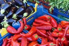 Fresh Organic Farm Produce. Fresh locally grown organic farm produce for sale at a weekly Greek farmers market, or laiki, with bright red peppers and black Stock Photo