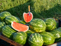 Fresh Organic Farm Produce, Watermelons. Fresh locally grown organic farm produce for sale at a weekly Greek farmers market, or laiki, with bright red cut Stock Photo