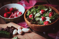 Fresh organic farm salad with fake mushrooms cut from reddish in wooden plate Stock Photos