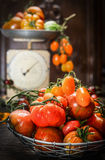 Fresh organic farm tomatoes over dark wooden background and  vintage scales Stock Photos