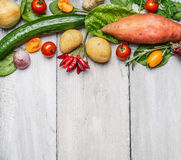 Fresh organic farm vegetables and ingredients for healthy cooking on white wooden background, border, top view. Stock Photo