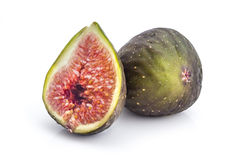 Fresh organic figs. Two fresh ripe organic figs, one cutted in half, isolated on white background Royalty Free Stock Photography