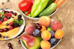 Fresh organic food - fruit and vegetable in bowl on table Stock Photography