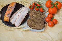 Fresh organic Food. Quick tasty snack. Close-up view of slices of pink bacon, pieces of rye bread, ripe red tomatoes. For appetizing background. Top view. With Stock Image