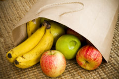 Fresh organic fruit. Fresh market fruit spilling out of a brown paper shopping bag Stock Photos