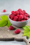 Fresh organic fruit - ripe raspberry with leaves on wood backgro Royalty Free Stock Photos