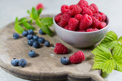 Fresh organic fruit - ripe raspberry with leaves on wood backgro Royalty Free Stock Photography