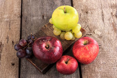 Fresh organic fruits , apples and grapes on the wooden table Royalty Free Stock Photos