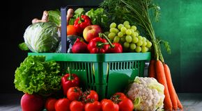 Fresh organic fruits and vegetables in plastic shopping basket.  stock images