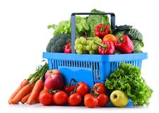Fresh organic fruits and vegetables in plastic shopping basket. Isolated on white royalty free stock photos