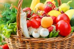 Fresh organic fruits and vegetables. Organic fruits and vegetables in a wicker basket royalty free stock photos