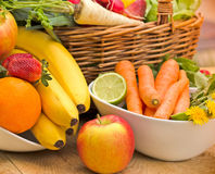 Fresh organic fruits and vegetables. In wicker basket and in bowls on a table Royalty Free Stock Photo