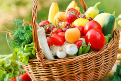 Fresh organic fruits and vegetables. Wicker basket is full of fresh fruits and vegetables royalty free stock photography