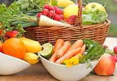 Fresh organic fruits and vegetables. In wicker basket on a table Royalty Free Stock Image