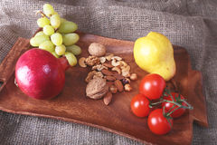 Fresh organic fruits and vegetables on wooden Serving tray. Assorted apple, pear, grapes, tomatoes and nuts. Royalty Free Stock Image
