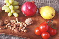 Fresh organic fruits and vegetables on wooden Serving tray. Assorted apple, pear, grapes, tomatoes and nuts. Royalty Free Stock Images