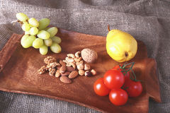 Fresh organic fruits and vegetables on wooden Serving tray. Assorted apple, pear, grapes, tomatoes and nuts. Stock Image