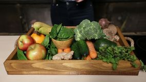 Fresh organic fruits and vegetables in wooden tray. Closeup colorful set of different fresh fruits and raw organic vegetables in wooden tray on the kitchen table stock video footage